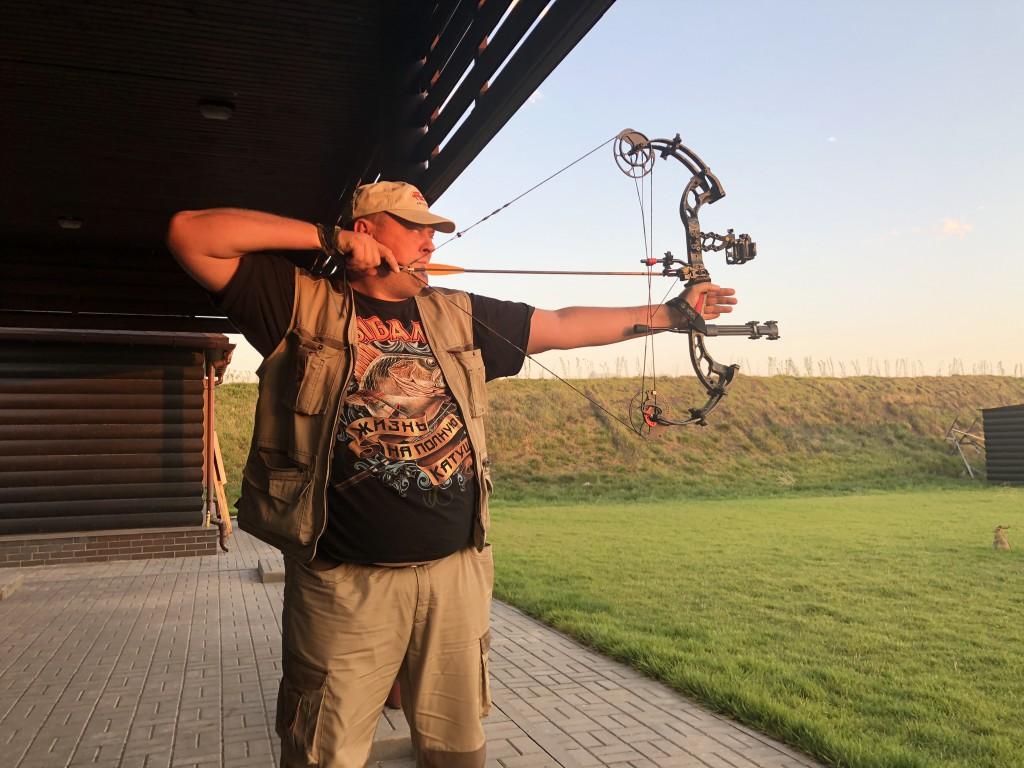 Инструктор показывает, как надо стрелять из лука